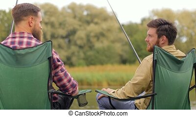 happy friends fishing and talking on lake - leisure and...
