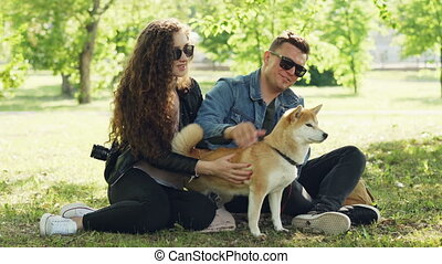 Happy friends girl and guy are caressing adorable dog,...
