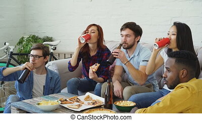 Happy friends have party talking and eating pizza. They clink bottles sitting on sofa at home