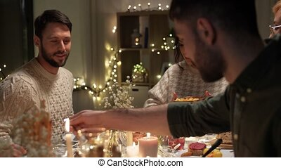 happy friends having christmas dinner at home - holidays, ...