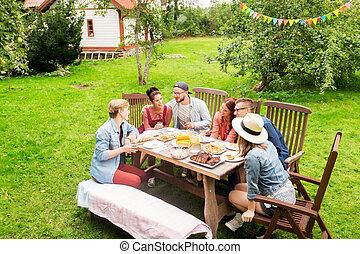 happy friends having dinner at summer garden party -...