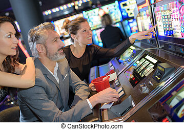 happy friends having fun together with slot machine
