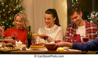 happy friends having home christmas dinner party - holidays...