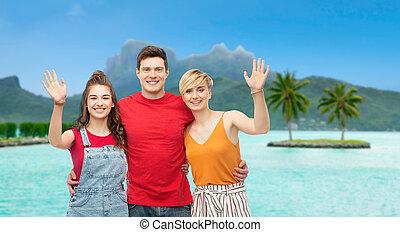 happy friends hugging over bora bora beach