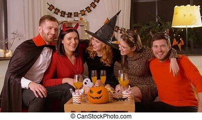 happy friends in halloween costumes at home party - ...