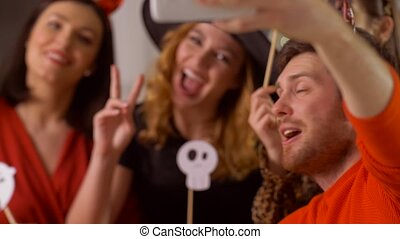 happy friends in halloween costumes taking selfie - ...