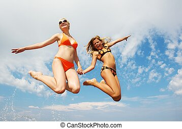 Happy friends jumping outdoors