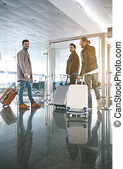 Happy friends keeping luggages in airport