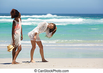 Happy friends laughing walking on the beach