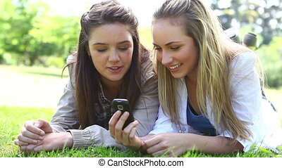 Happy friends looking at a text