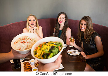Happy friends looking at the salad