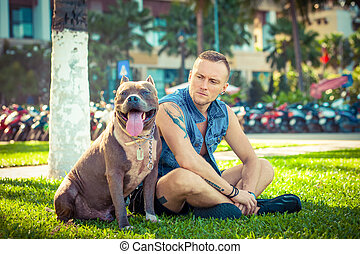 Happy friends man and dog american pit bull terrier sitting on grass in park
