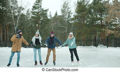 Happy friends men and women ice-skating in snowy park having fun together