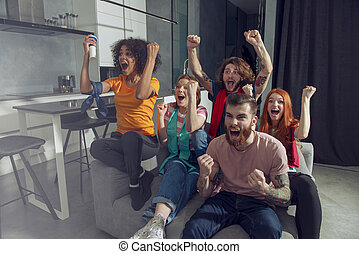 Happy friends of football fans watching soccer on tv and celebrating victory.