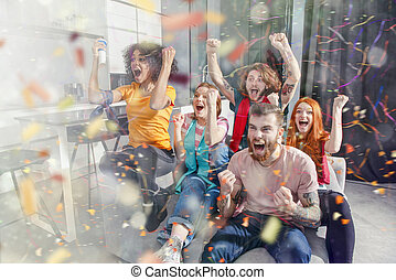 Happy friends of football fans watching soccer on tv and celebrating victory with falling confetti
