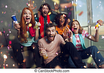 Happy friends of football fans watching soccer on tv and celebrating victory with falling confetti.