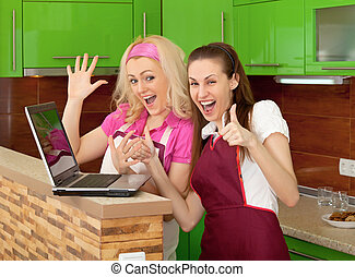 Happy friends on kitchen with a laptop