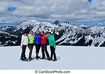 Happy friends on mountain top snowshoeing. Friendship concept. Whitler Blackcomb. Vancouver. British Columbia. Canada.