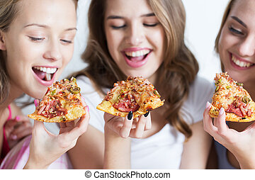 happy friends or teen girls eating pizza at home