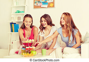 happy friends or teen girls eating sweets at home -...