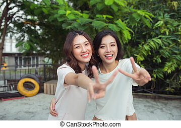 Happy friends or teenage girls having fun outdoors
