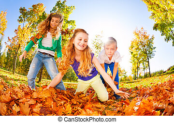 Happy friends playing red leaves in the forest