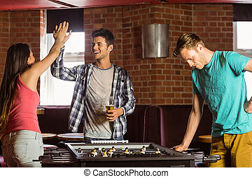 Happy friends playing table football