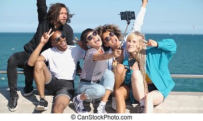 Happy friends posing for selfie on seafront - Cool young...