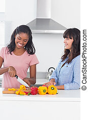 Happy friends preparing peppers for