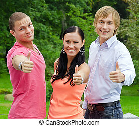 Happy friends raising hands with thumb up in the park