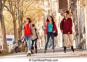 Happy friends rollerblading on sidewalk in autumn
