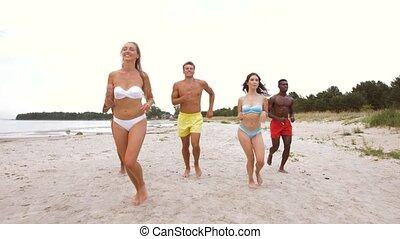 happy friends running on summer beach - friendship, summer...