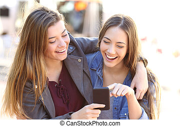 Happy friends sharing a smart phone