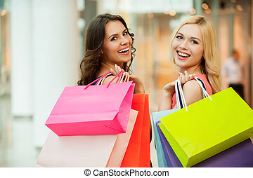 Happy friends shopping. Two beautiful young women enjoying ...