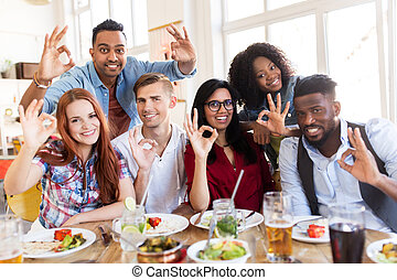 happy friends showing ok hand sign at restaurant - eating,...
