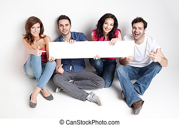 happy friends showing white banner - four friends showing a ...