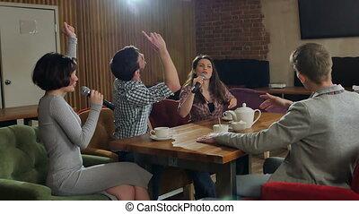 Happy friends singing karaoke together in a bar....