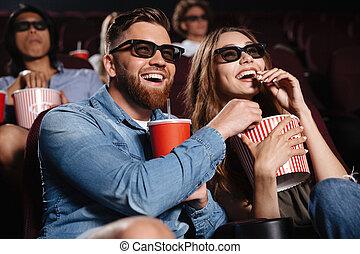Happy friends sitting in cinema watch film eating popcorn -...