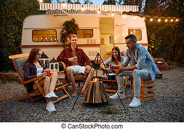 Happy friends sitting near campfire in the evening, picnic at camping in the forest. Youth having summer adventure on rv, camping-car on background. Two couples leisures, travelling with trailer
