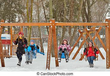 Happy friends sitting on swing in park