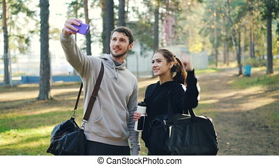 Happy friends sportive young people are taking selfie using smartphone after outdoor practice in park. Man and woman are holding bags and posing for camera.