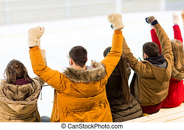 happy friends supporting team on ice rink arena - people,...