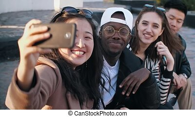 Happy friends taking a photo - Happy multiethnic friends...