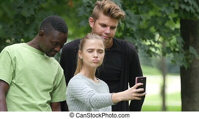 Happy friends taking a selfie on a blue sky in campus lawn, african man. slow motion