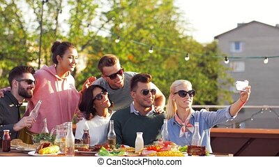 happy friends taking selfie at rooftop party - leisure and...