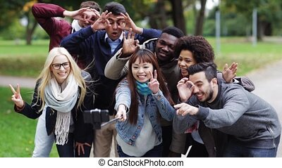happy friends taking selfie by smartphone in park