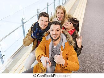 happy friends taking selfie on skating rink - people,...