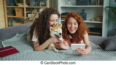 Happy friends taking selfie with adorable puppy lying on sofa using smartphone