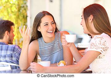 Happy friends talking in a coffee shop terrace