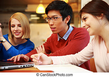 Happy friends using laptop together